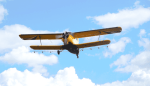 Yellow single engine biplane with blue sky and white clouds in background